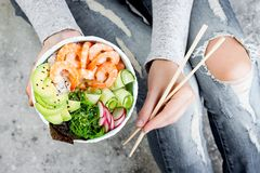 Girl in jeans holding shrimp poke bowl with seaweed, avocado, cucumber, radish, sesame seeds stock photos