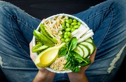 Girl in jeans holding vegan, detox green Buddha bowl with quinoa, avocado, cucumber, spinach, tomatoes, mung bean sprouts, edamame. Beans, daikon radish. Top stock images