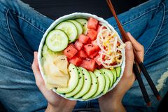 Girl in jeans holding vegan watermelon poke bowl with avocado, cucumber, mung bean sprouts and pickled ginger. Top view, overhead. Stock Photo