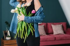 Girl in the blue shirt hiding behind flowers tulips in hands on wooden background. A girl in a jeans holds a bouquet of tulips in stock photos