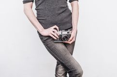 Girl in jeans holds an old vintage film camera at the hips royalty free stock image