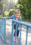 Girl in a jeans jacket draws with colored chalks Royalty Free Stock Images