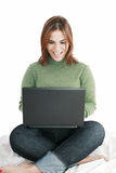 Girl in jeans with laptop sitting Stock Images