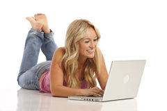 Girl with jeans laying on floor with laptop Stock Photo