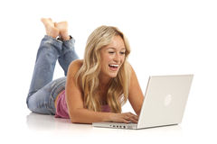 Girl with jeans laying on floor with laptop Royalty Free Stock Photo