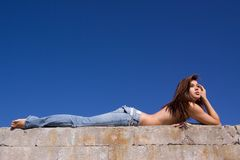 Girl in jeans lying on concrete. Topless girl in blue jeans lying on concrete block Stock Image
