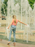 Girl in jeans plays with the water jets in the fountain. Stock Images