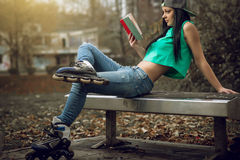 Girl in jeans reading a book on bench Stock Images