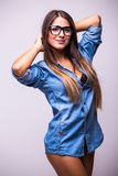Girl in jeans shirt with glasses posing with different gesture in studio stock images