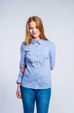 Girl in jeans and shirt, young woman, studio shot. Teenage girl in jeans and blue checked shirt, young woman, studio shot on gray background stock images