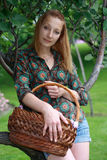 Girl in jeans shorts with basket in garden Stock Image