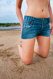 Girl in jeans shorts on the beach Royalty Free Stock Photos