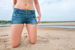 Girl in jeans shorts on the beach Royalty Free Stock Image