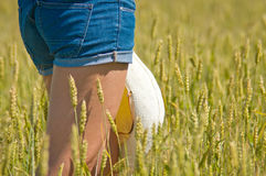 Girl in jeans shorts in the field Royalty Free Stock Image