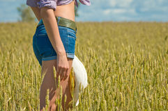 Girl in jeans shorts in the field Stock Photos