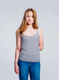 Girl in jeans and singlet, young woman, studio shot. Teenage girl in jeans and blue tank top, young woman, studio shot on gray background stock image