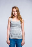 Girl in jeans and singlet, young woman, studio shot. Teenage girl in jeans and gray tank top, young woman, studio shot on gray background stock images
