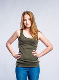 Girl in jeans and singlet, young woman, studio shot. Teenage girl in jeans and khaki tank top, young woman, studio shot on gray background stock images