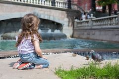 Girl in jeans sits near the fountain and feeding birds. Cookies royalty free stock photos