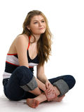 Girl in jeans sits on a white. Beautiful girl in jeans sits on a white background Royalty Free Stock Image