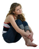 Girl in jeans sits on a white Stock Image