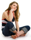 Girl in jeans sits on a white Stock Photography
