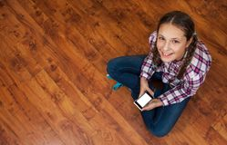 Girl in jeans sits on wooden floor and holding a smartphone. Concept of teenage life and gadgets. Top view with copy space. Royalty Free Stock Image