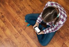 Girl in jeans sits on wooden floor and holding a smartphone. Concept of teenage life and gadgets. Top view with copy space. Royalty Free Stock Photos