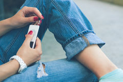 Girl in jeans sitting on the bench and connect the headphones to. A young woman in jeans sitting on the bench and connect the headphones to her music player Royalty Free Stock Photo