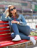 Girl in jeans sitting on a bench in the street Royalty Free Stock Images