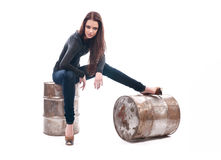 Girl in jeans sitting on the iron barrel Royalty Free Stock Image