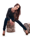 Girl in jeans sitting on an iron barrel Stock Images