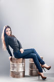 Girl in jeans sitting on metal barrel Stock Image