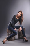 Girl in jeans sitting on metal barrel Stock Photo