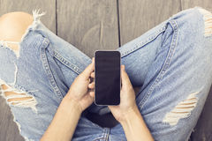 Girl in jeans with smartphone on the wooden floor Stock Photo