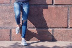 Girl in jeans and sneakers on the street. A girl in jeans and sneakers is standing near a stone wall Royalty Free Stock Image