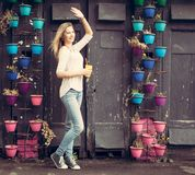 Girl in jeans and sneakers with a yellow cup waving near the wall with flowers. Outdoor Stock Photography