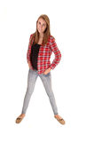 Girl in jeans standing. A young woman with long brunette hair standing in the studio in jeans and a checkered red shirt, for white background stock images