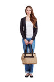 Girl in jeans standing and holding a bag Royalty Free Stock Image