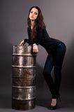 Girl in jeans standing near an iron barrel Royalty Free Stock Photography