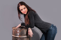 Girl in jeans standing near the iron barrel Stock Photography