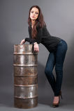 Girl in jeans standing near the iron barrel Stock Images