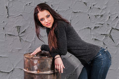 Girl in jeans standing near the iron barrel Royalty Free Stock Photography