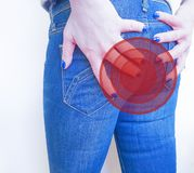 Girl in jeans suffers hemorrhoids concept unhealthy pain stock photo