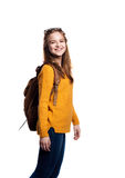 Girl in jeans and sweater, young woman, studio shot. Teenage girl in jeans, mustard yellow sweater, with backpack on back, young woman, studio shot on white stock image