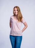 Girl in jeans and t-shirt, young woman, studio shot. Teenage girl in jeans and pink t-shirt, young woman, studio shot on gray background royalty free stock photo