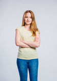 Girl in jeans and t-shirt, young woman, studio shot. Teenage girl in jeans and yellow t-shirt, young woman, studio shot on gray background stock photo