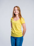 Girl in jeans and t-shirt, young woman, studio shot. Teenage girl in jeans and yellow t-shirt, young woman, studio shot on gray background royalty free stock images