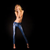 Girl in jeans topless covered hands. Posing on black isolated background Stock Images