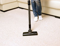 Girl in jeans vacuuming the house. royalty free stock photography